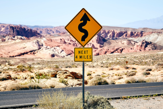 Road in the desert with a sign saying curvy road ahead for four miles.